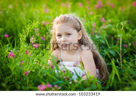 Adorable kid on the meadow with pink field flowers - stock photo