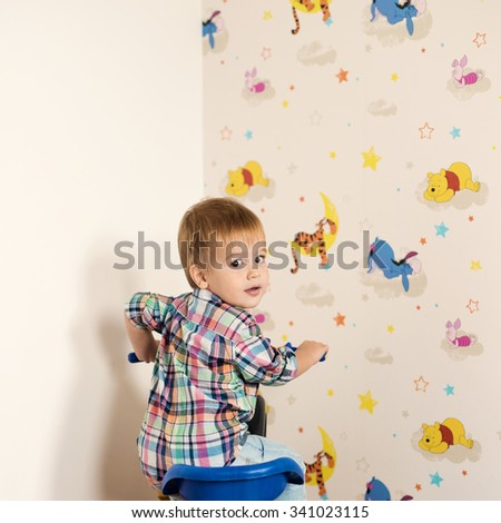 Adorable kid playing in a room with his toys. He is sitting on his bike. Very shallow depth of field. - stock photo