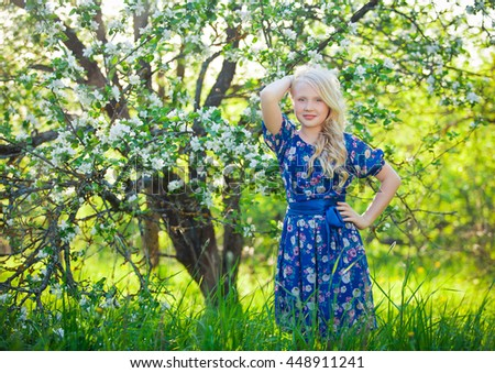 Adorable kid playing in nature. Cute little child, blonde toddler girl playing in blooming cherry garden on beautiful spring or summer day - stock photo