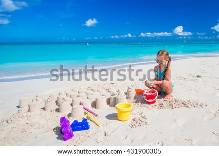 Adorable kid playing with beach toys on white beach