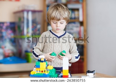 Adorable kid playing with lots of colorful plastic blocks indoor. Child having fun with building and creating. - stock photo