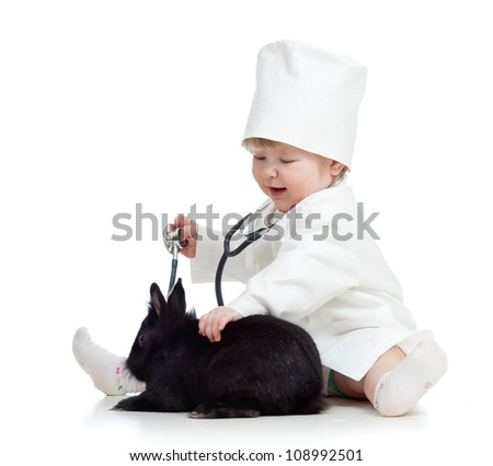 Adorable kid with clothes of doctor. Girl is playing with pet bunny - stock photo