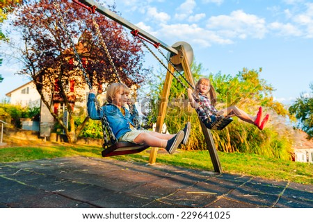 Adorable kids having fun outdoors on sunset, playing on a swing - stock photo