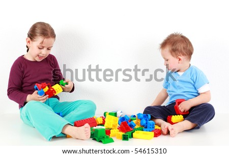 Adorable kids playing together with blocks - stock photo