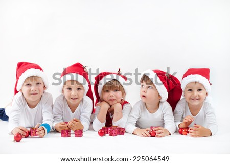 Adorable kids with santa hat, smiling at the camera, isolated on white background