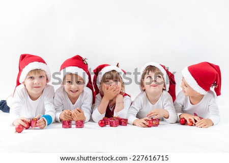 Adorable kids with santa hat, smiling at the camera, isolated on white background - stock photo