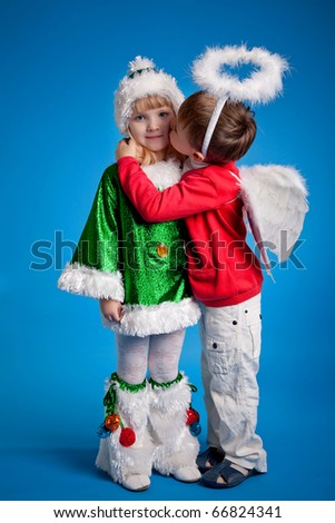 Adorable kissing kids in New Year's costumes - stock photo
