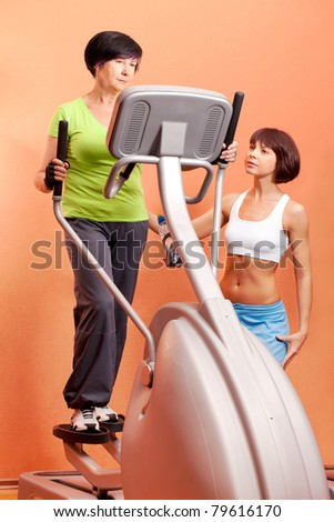 Adorable lady on cardio machine in the gym - stock photo