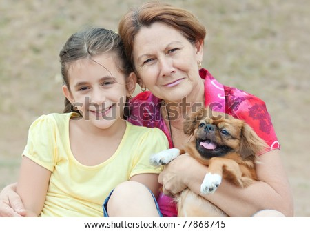 Adorable latin girl, her grandmother and the family dog in a park - stock photo