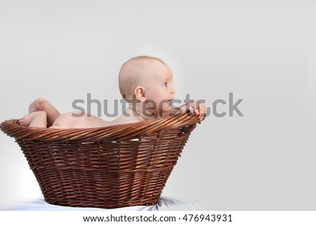 Adorable laughing baby in a basket.