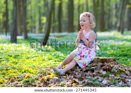 Adorable laughing child, blonde healthy toddler girl wearing beautiful summer dress enjoying nature, playing and hiking in spring forest, picking, touching and holding snowdrops flowers - stock photo
