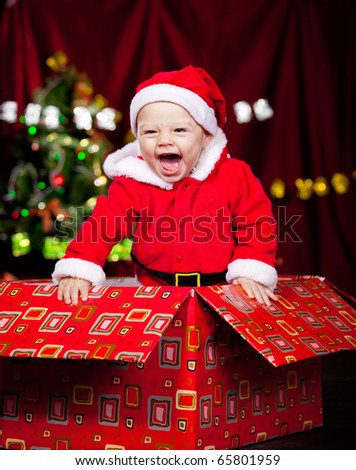 Adorable laughing kid in a large present box - stock photo