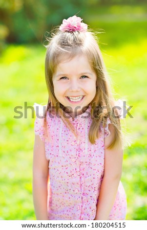 Adorable laughing little girl with long blond hair, outdoor portrait in summer park - stock photo