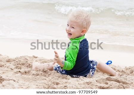 adorable laughing toddler at the tropical beach