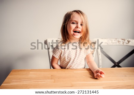 adorable laughing toddler girl having fun at home in the kitchen - stock photo