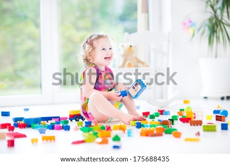 Adorable laughing toddler girl playing with colorful blocks sitting on a floor in a sunny bedroom with a big window - stock photo