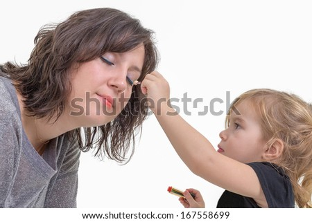 Adorable litte blond girl applying makeup to her mother putting eyeshadow on her eyes, isolated on white - stock photo