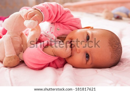 Adorable little african american baby girl playing with a plush - Black people - stock photo