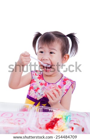 Adorable little asian (thai) girl enjoy eating her birthday cake at the table, lip dirty with strawberry sauce, isolated on white background, shot in studio - stock photo