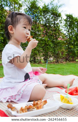 Adorable little asian (thai) girl enjoy eating her lunch in the park, child eating fried chicken, chinese steamed dumpling and watermelon over blur green nature background - stock photo