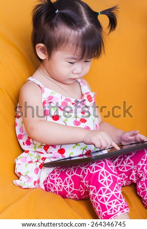Adorable little asian (thai) girl using digital tablet, child finger point at computer tablet, concept about education and learning, studio shot - stock photo
