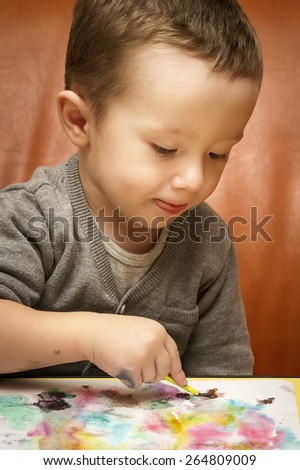 Adorable little baby boy painting concentrated  with watercolors on a white paper on the table, holding a brush - stock photo