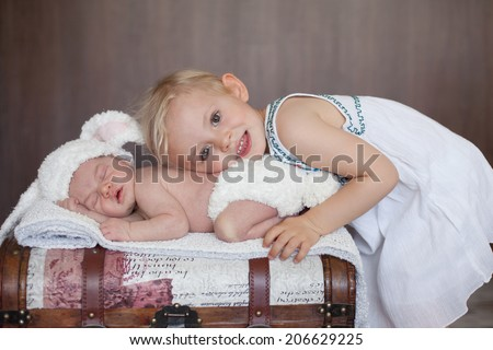 Adorable little baby boy, sleeping, his big sister cuddling him - stock photo