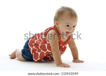 Adorable little baby crawling with a determined look