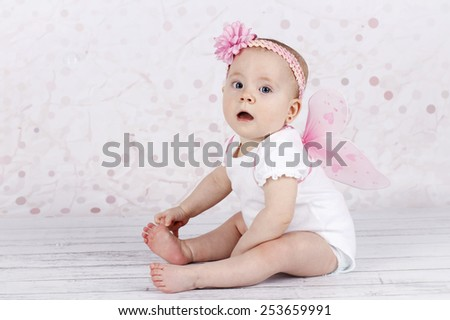 Adorable little baby girl with butterfly wings - stock photo