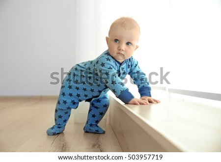 Adorable little baby standing beside wooden windowsill
