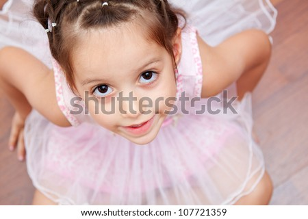adorable little ballerina looking up to the camera - stock photo