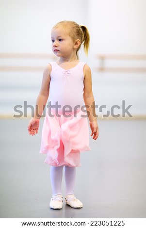 Adorable little ballerina wearing pink leotard in a dancing school - stock photo