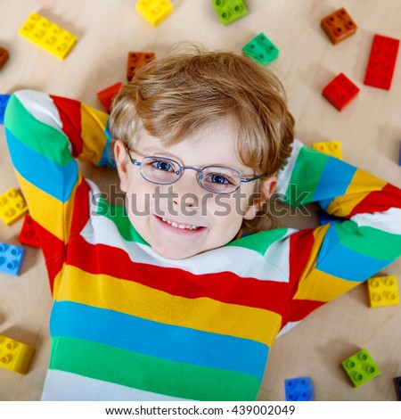 Adorable little blond child with glasses playing with lots of colorful plastic blocks indoor. Happy Kid boy wearing colorful shirt and having fun with building and creating. - stock photo