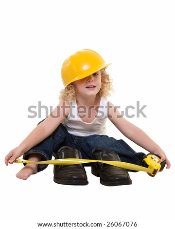 Adorable little blond curly hair three year old boy wearing white muscle top and jeans and yellow hard hat sitting on floor with tape measure measuring grown up mans shoes - stock photo
