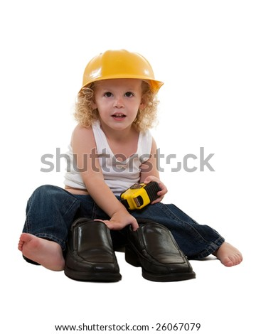 Adorable little blond curly hair three year old boy wearing white muscle top and jeans and yellow hard hat sitting on floor with tape measure and grown up mans shoes - stock photo