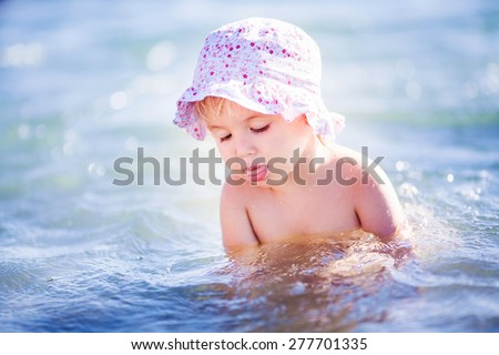 Adorable little blond girl at beach during summer vacation - stock photo