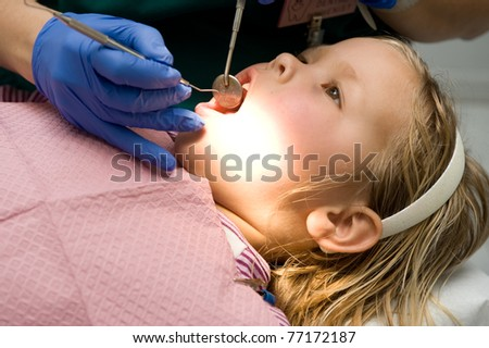 Adorable little blond girl getting her teeth checked at the dentist - stock photo