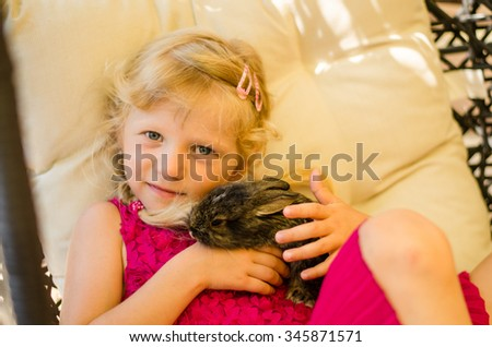 adorable little blond girl holding a bunny rabbit pet