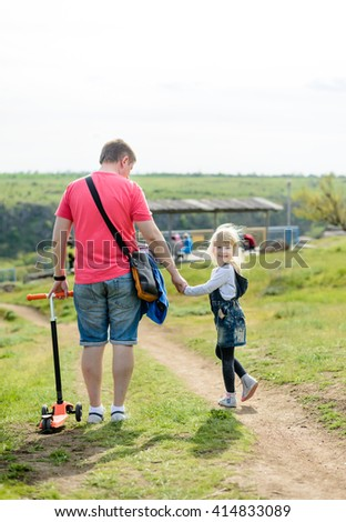 Adorable little blond girl holding hands with her father as they walk along a rural path turning to look back and smile happily at the camera
