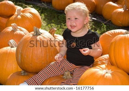 Adorable Little Blond Girl in Pumpkin Patch