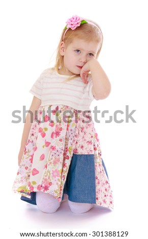 Adorable little blond girl kneeling on something deep in thought.-Isolated on white background - stock photo