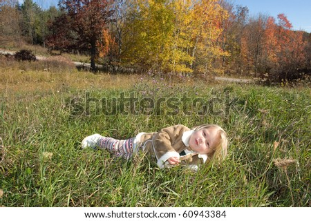 Adorable little blond girl laying in the grass outside with trees changing colors in autumn - stock photo