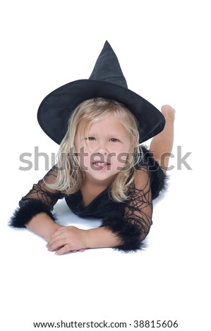 Adorable little blond girl laying on her stomach wearing a witch costume - stock photo