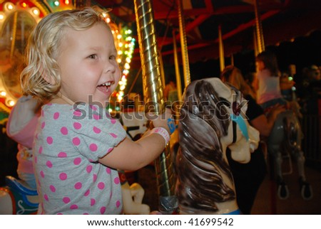 Adorable little blond girl riding on a carousel horse - stock photo