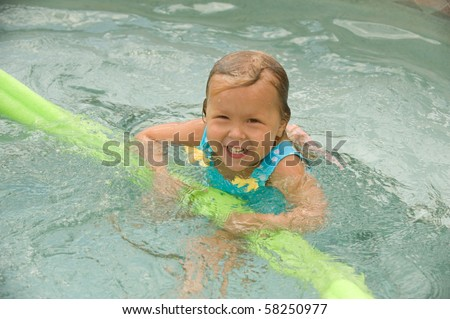 Adorable little blond girl smiling in the swimming pool - stock photo