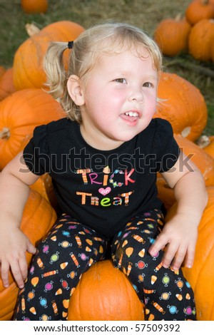 Adorable little blond girl smiling sitting in a pumpkin patch - stock photo