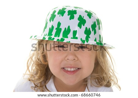 Adorable little blond girl smiling wearing a shamrock hat for St. Patrick's Day in the studio - stock photo