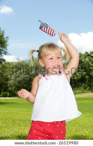 Adorable little blond girl waving American flag - stock photo