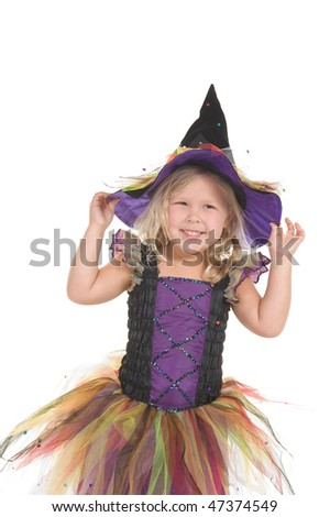 Adorable little blond girl wearing a witch costume smiling at the camera - stock photo