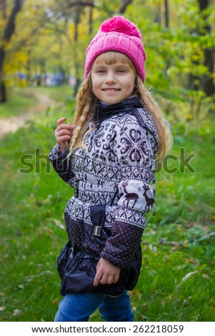 Adorable little blond girl with long blond hair in autumn park. Beautiful little young baby in a pink hat - stock photo